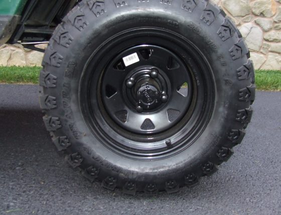 closeup of black golf cart wheel and used tire parked on asphalt surface