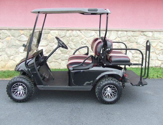 black ezgo golf cart parked in front of green grass sitting next to stone building