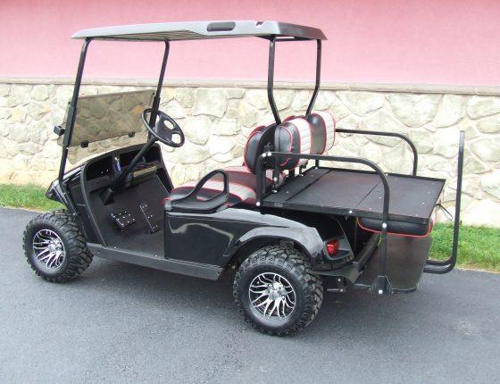 side view of black ezgo golf cart parked on dark asphalt surface