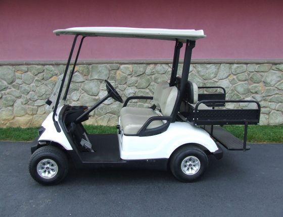 rental golf cart with two rear add on seats parked on asphalt surface next to stone building