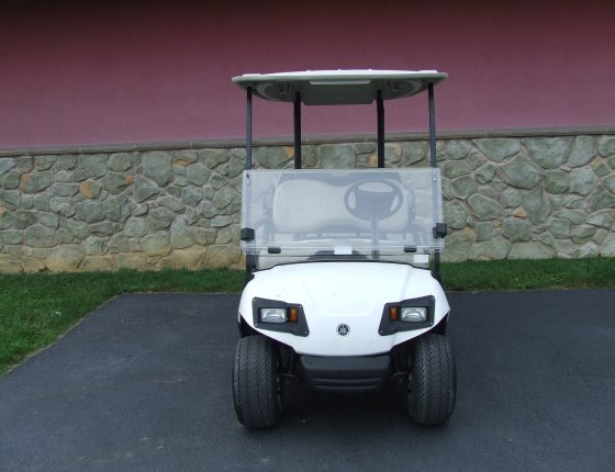 white yamaha two seater golf cart parked on asphalt surface in front of stone building