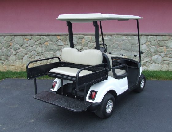 white golf cart for rent parked on asphalt surface standing next to large building
