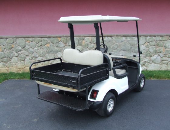 rear view of white yamaha golf cart parked next to stone building
